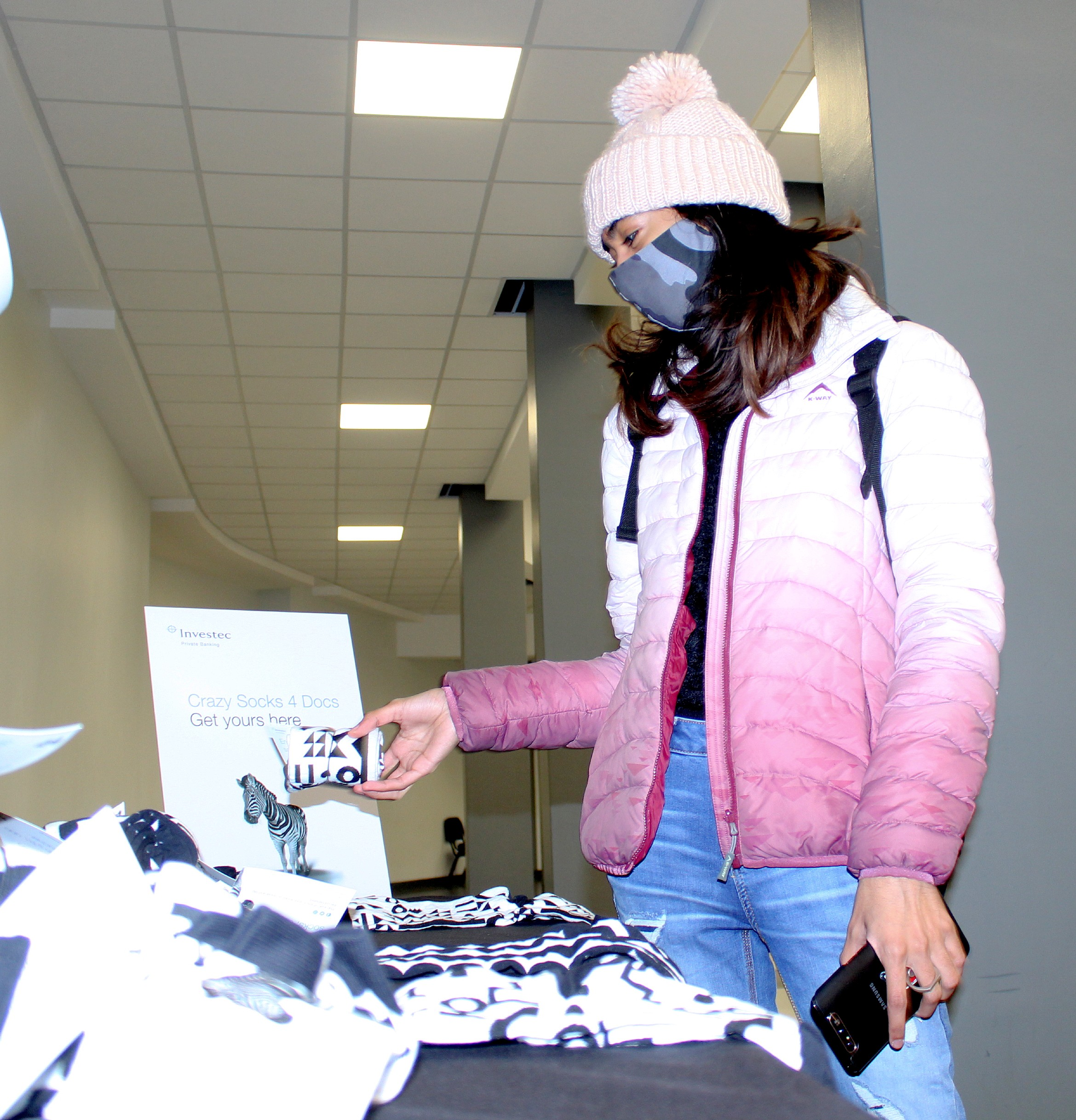 Sanam Bhagwandeen, a third-year student, choosing her pair of socks from the Investec Private Banking socks table.
