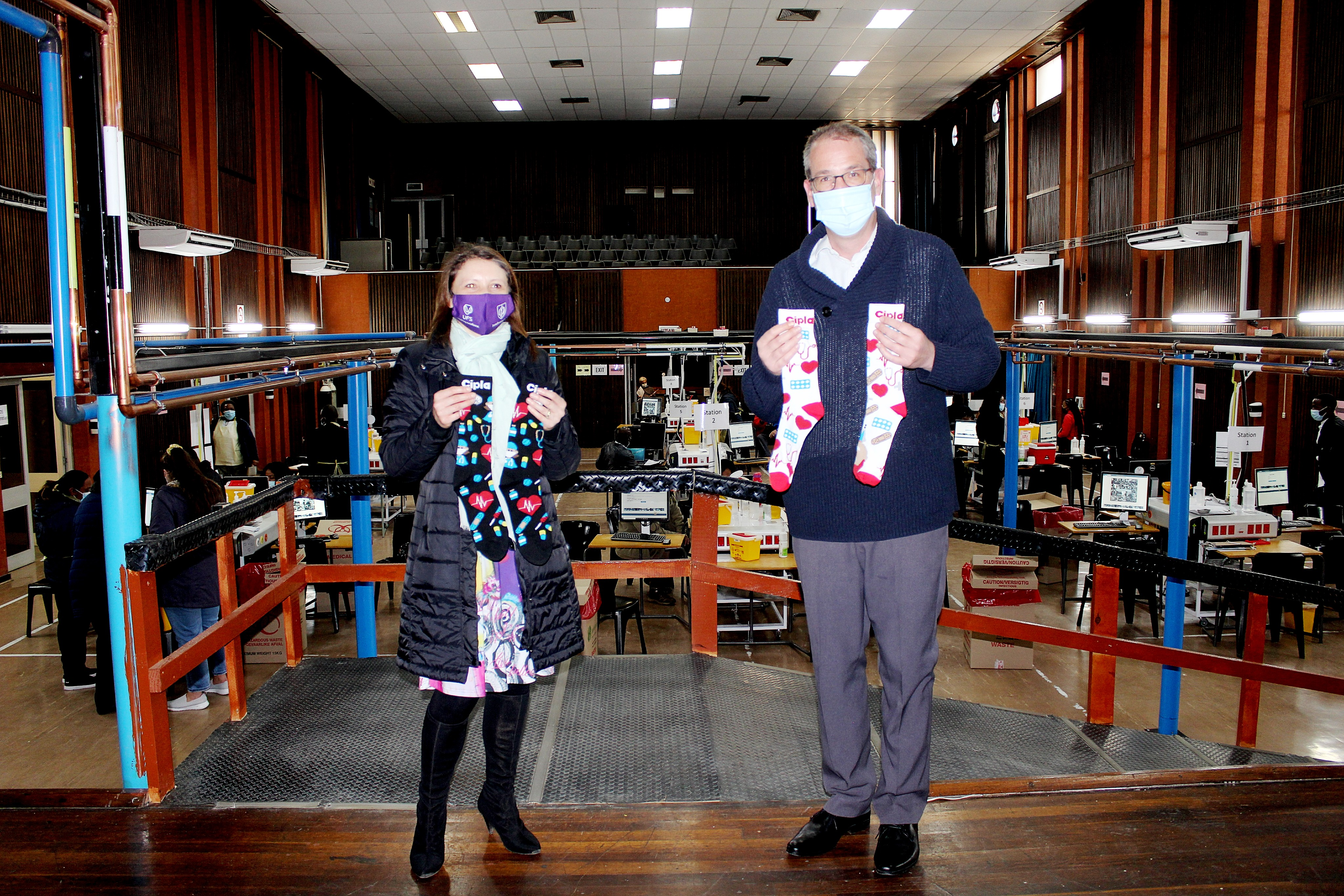 Dr Nicholas Pearce, Head of Surgery at the UFS – who is also heading the Universitas Hospital COVID-19 Task Team – receives a donation of crazy socks from Angela Vorster, Clinical Psychologist in the School of Clinical Medicine