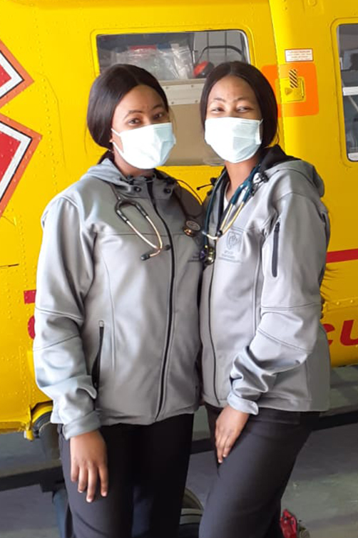 Drs Keitumetse (left) and Boitumelo (right) Molise in front of a medical rescue helicopter