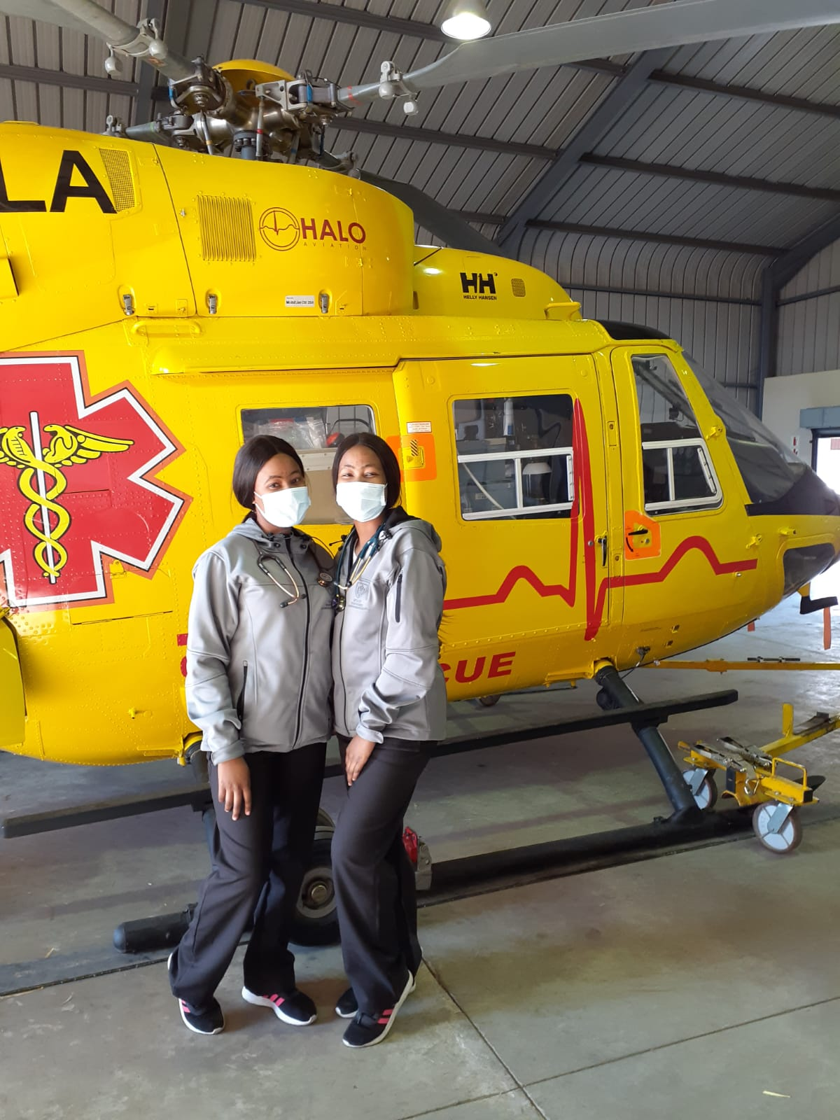 Drs Keitumetse (left) and Boitumelo (right) Molise pose next to a medical rescue helicopter