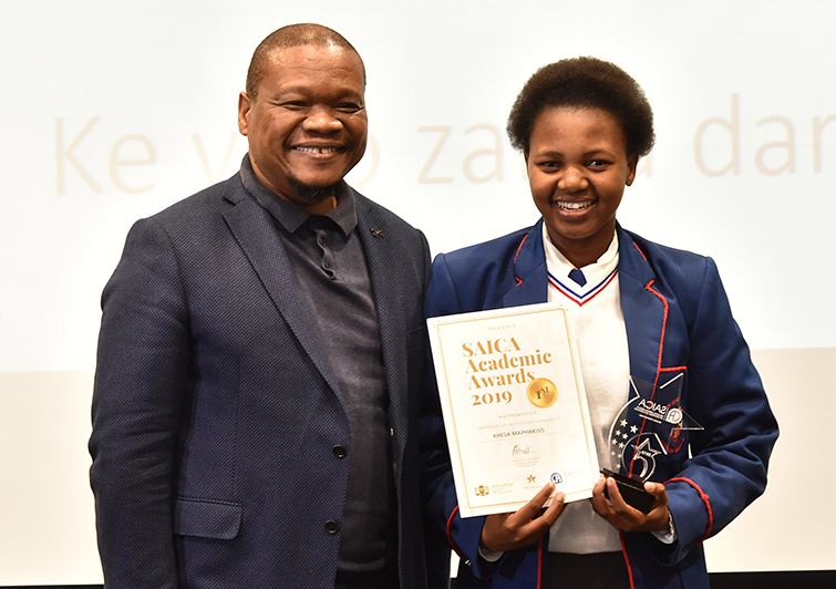 MEC for Education, Dr Tate Makgoe, presents an award to Khesa Maphakiso from Beacon High School at the ceremony.