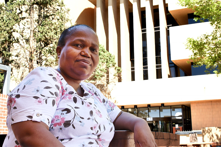 Nthabiseng Kotsokoane in front of the Sasol Library on the Bloemfontein Campus of the University of the Free State. She is wearing a pink blouse with floral patterns and leaning with her left elbow against a ledge whilst looking into the camera.