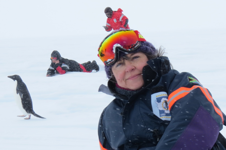 Prof Linda Basson recently returned from a three-month research expedition in Antarctica. Here she is, relaxing on the ice with the ever-inquisitive Adelie penguins having a gander at these strangers in their snowy world.