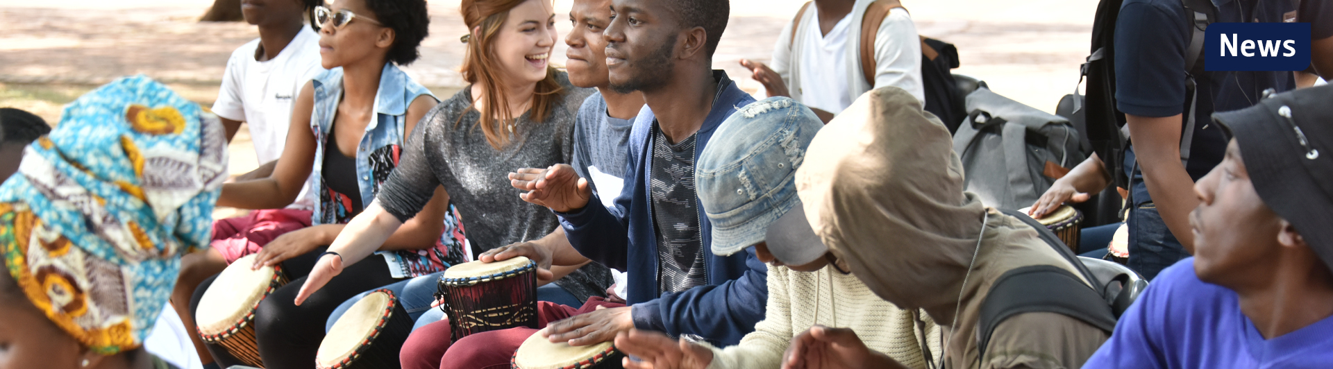 People sitting in a row, learning how to use traditional African drums.