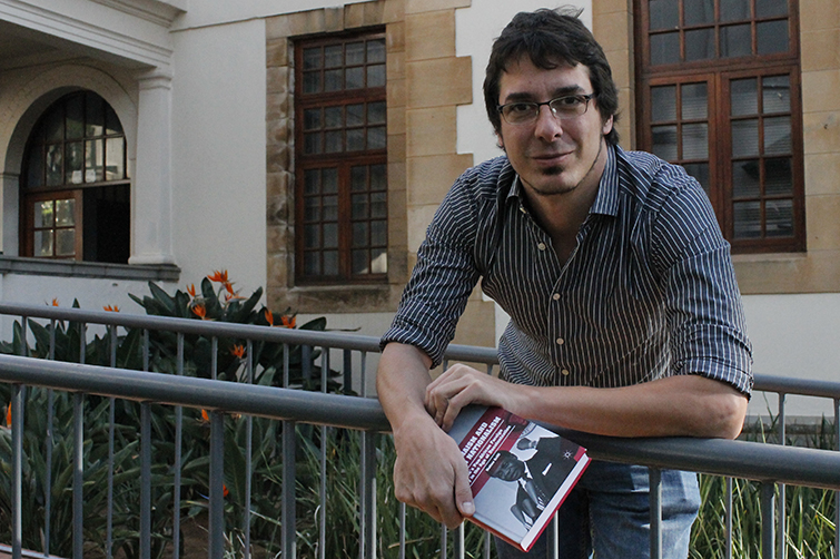 Dr Matteo Grilli with his first book in front of the North Block on the Bloemfontein Campus.